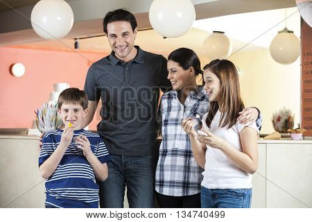 Boy Having Ice Cream While Standing With Family At Parlor