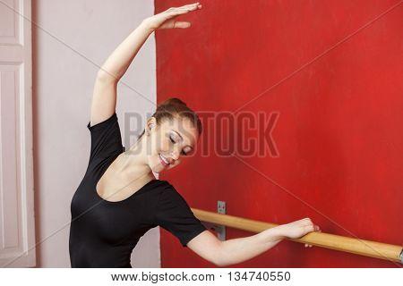 Ballet Dancer Stretching Hand At Barre In Studio