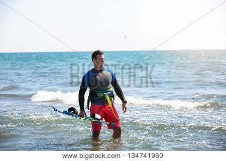 Athletic man riding on kite surf board on a sea waves