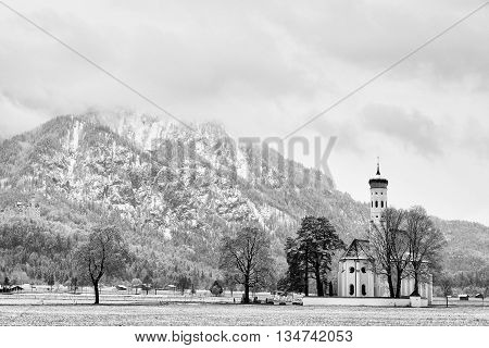 Old Church With High Bell Tower And Graveyard Bellow Mountains.