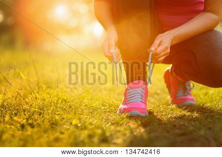 Woman Lacing Running Shoes Before Workout. Lens Flare.
