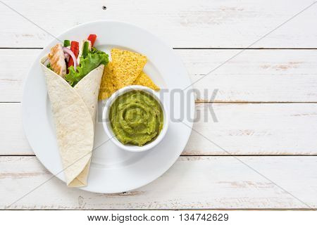 Mexican chicken fajitas with peppers lettuce and onion on a plate and white wooden background