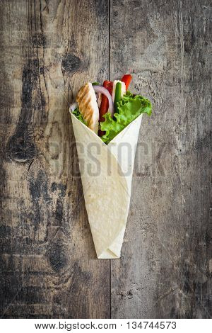 Mexican chicken fajita with peppers lettuce and onion on a rustic wooden table