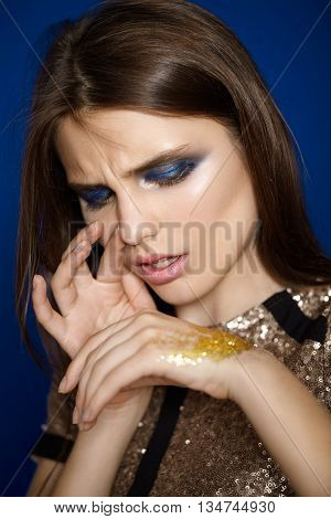 Beautiful fashion close-up portrait of a girl who sniffs sequins.