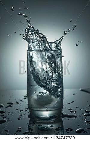 Splashes in a glass of pure cold water with an ice cube