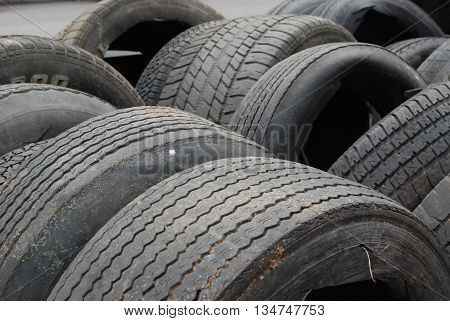 Ranks of vulcanized rubber tires awaiting recycling.