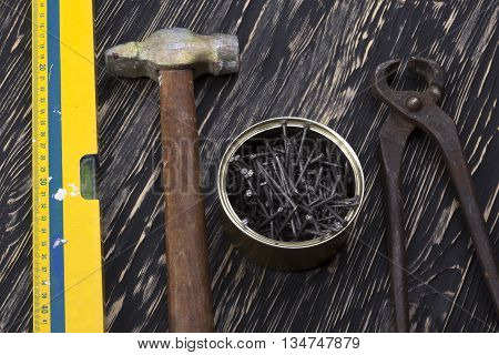Construction tools: level, hammer pliers and nails