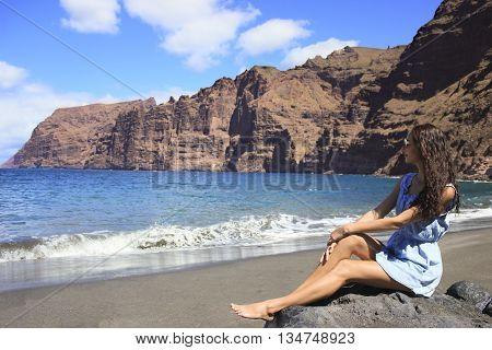 Beautiful dark-haired girl sit on the beach with black sand surrounded by mountains