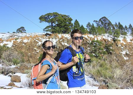 Woman and man standing with backpacks on landscape - snowy mountain and trees