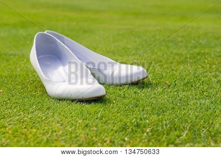 particular of white wedding shoes on grass