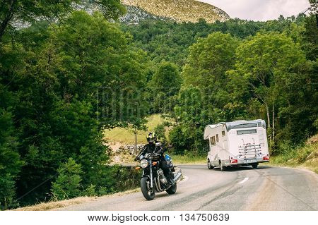 Verdon, France - June 29, 2015: Motorhome car and rider on bike moving along a mountain road on background of French mountain nature landscape.