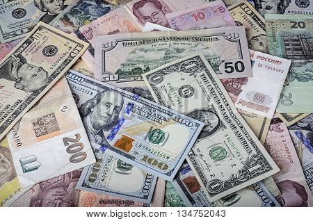 A collection of various foreign currencies from countries spanning the globe. Many different currencies as colorful background concept global money. Soft selective focus and shallow depth of field