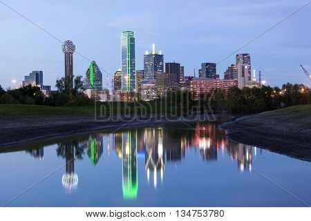 Dallas downtown skyline illuminated at night with reflection in the Trinity River. Texas United States