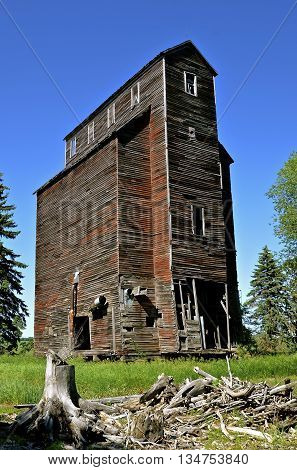 A deteriorating old elevator constructed with wood  stands empty, falling into ruins, and leaving memories of a past era