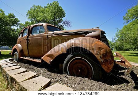 An old rusty wrecked car of the 40's with a flat tire is on display