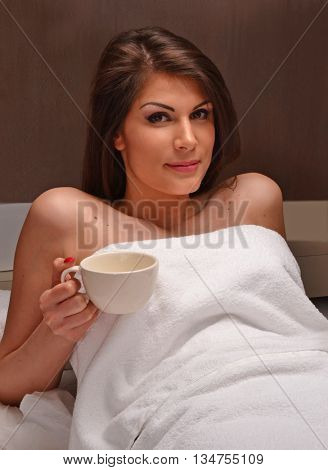 Beautiful latin woman drinking tea cup after relax on spa center and body treatment.bed.