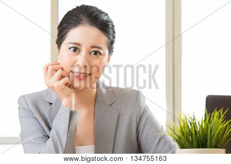 Successful Asian Female Entrepreneur Sitting And Smiling At Desk