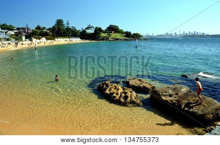 Sydney - October 19, 2014. People are swimming on a warm day in spring time at Camp Cove. Sydney city in the background.