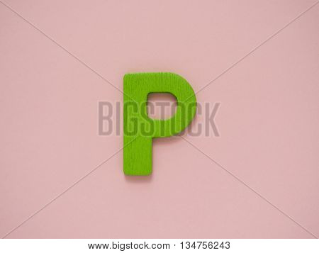 Capital letter P. Green letter P from wood on pink background.