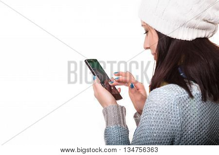 Smiling Winter Hipster Girl in Knitted Sweater and Beanie Hat with Mobile Phone Isolated on White. Teenage Communication Concept