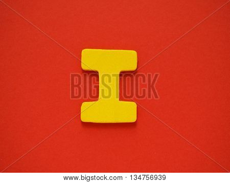 Capital letter I. Yellow letter I from wood on red background. Alphabet vowel.