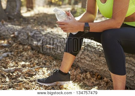 Female runner in a forest takes a break, low section crop