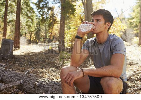 Male runner in a forest takes a break to sit and drink water