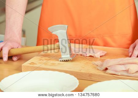 Man Beating Chicken Meat On Wooden Board
