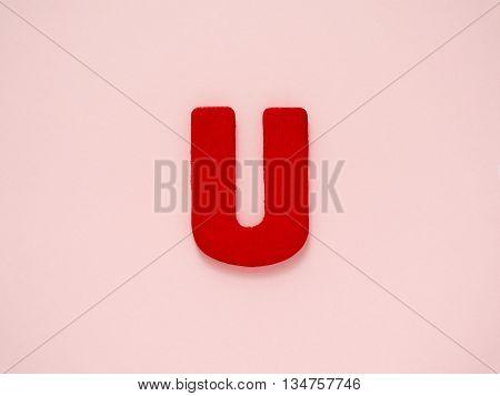Capital letter U. Red letter U from wood on pink background. Alphabet vowel.