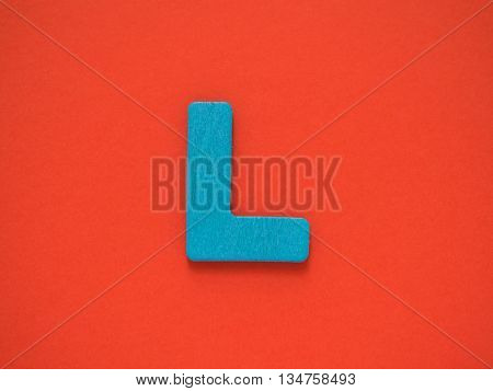Capital letter L. Blue letter L from wood on red background.