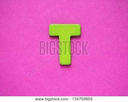 Capital letter T. Green letter T from wood on purple background.