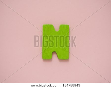 Capital letter N. Green letter n from wood on pink background.