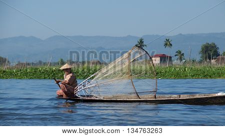 Inle Lake, Myanmar  - October 2015: the Burmese fisherman using one pole and net for fishing on Inle Lake, Myanmar.