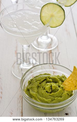 Margarita cocktail, guacamole and nachos on a white wooden table