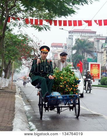HA NOI, VIET NAM, January 28, 2016 cyclo man, on the streets of Ha Noi, Vietnam. Go Army soldiers, carrying twigs to dig, home