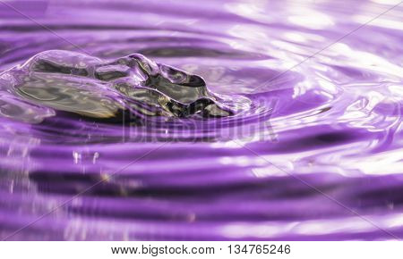 Purple reflections on water after a water drop leaving metallic effect wave
