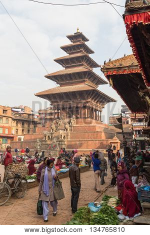 Bhaktapur, Nepal - December 5, 2014: People buying and selling goods at the market on Taumadhi Square.