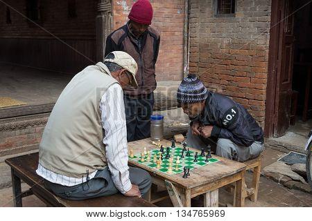 Bhaktapur, Nepal - December 5, 2014: Elderly men playing chess in the streets.