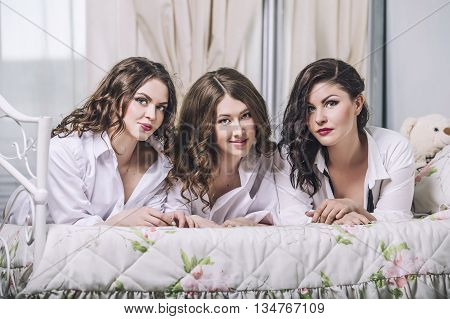Three Beautiful Young Women Friends Chatting In The Bedroom In  Shirts