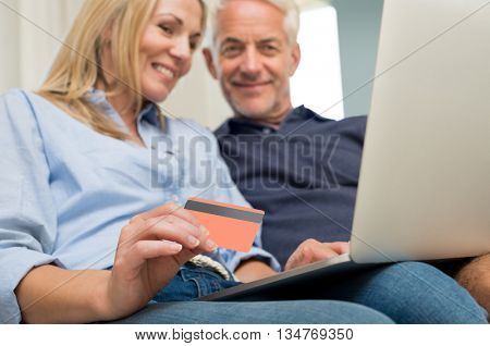 Senior couple making shopping online with credit card. Happy husband and smiling wife buying on internet. Close up of credit card in woman hand while shopping on internet. Banking online concept.