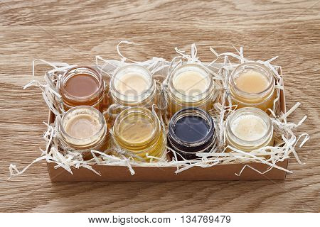 A paper box with eight different kinds of honey decorated with sawdust.