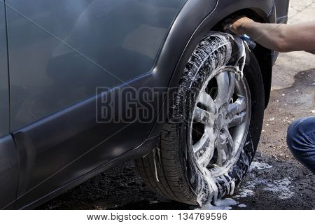car wheel is washing in soap suds