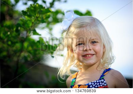 Blonde caucasian girl playing outside in cute dress