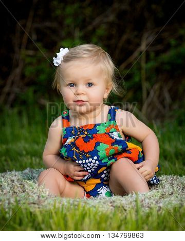 Cute toddler sitting in flowered dress outside in grass