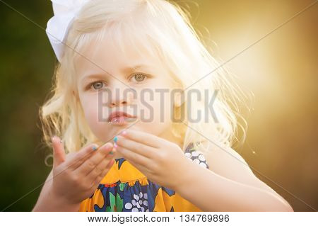 Blonde little 3 year old girl with glitter on lips and painted fingernails