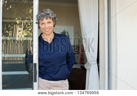 Portrait of smiling mature woman leaning against door and looking at camera. Satisfied senior business woman in formals enjoying.