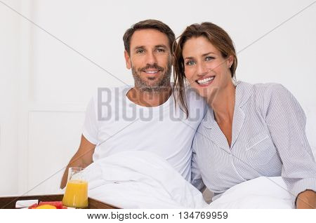Happy mature couple enjoying breakfast on bed in the morning. Couple eating breakfast and juice on bed. Cheerful couple sitting on bed and looking at camera.