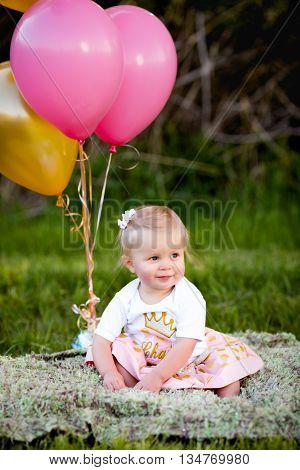 Happy little blonde caucasian girl outside with yellow and pink balloons playing and having fun