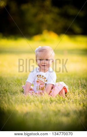 Happy blonde toddler sits alone in grass wearing pink and white dress