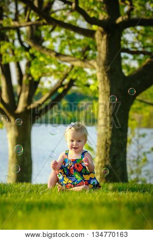 toddler sitting outside playing with bubbles in park by lake and trees
